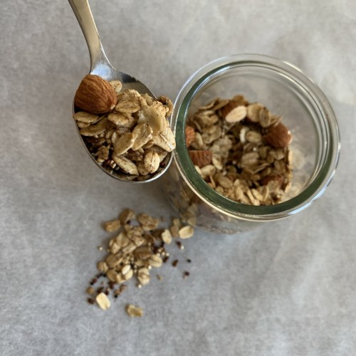 vegan granola on a spoon above a glass dish filled with the granola