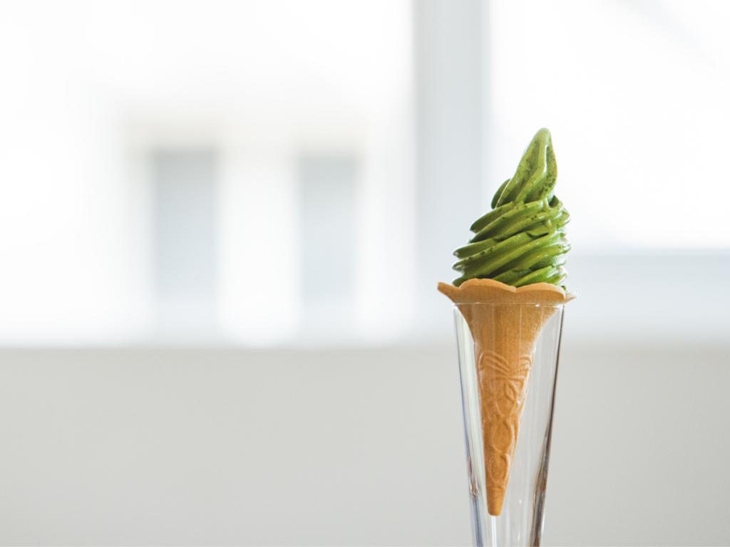Vegan matcha ice cream in a soft serve ice cream cone